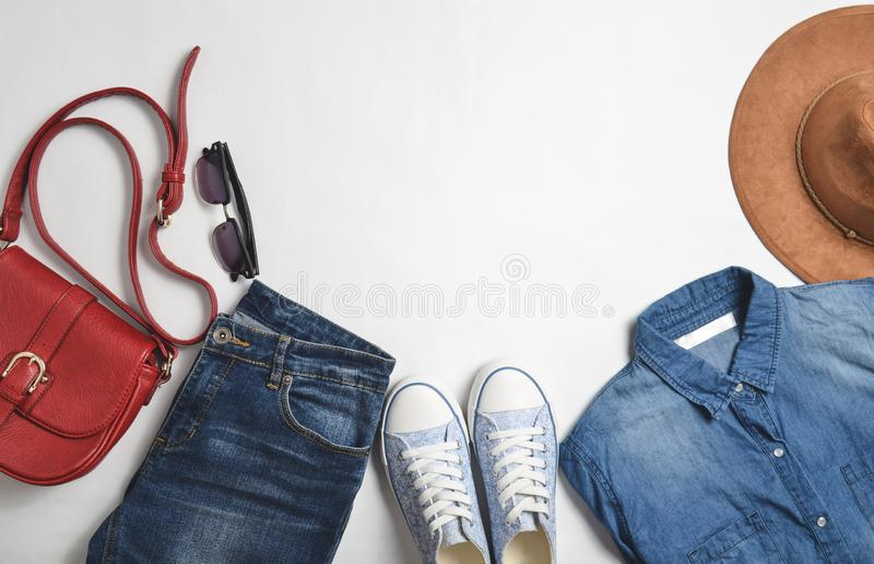 Women& x27;s fashion clothing and accessories. Jeans, denim shirt, sneakers, felt hat, leather bag, sunglasses, layout. On a white background. Top view, flat stock image