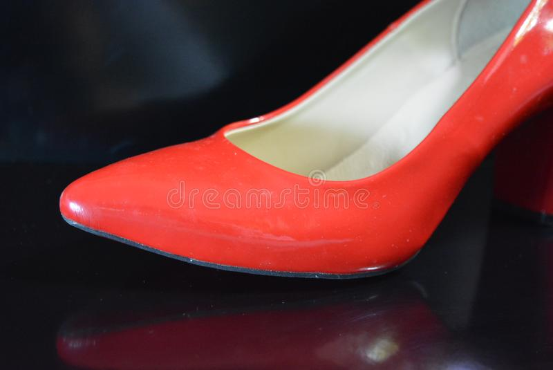 A very bright pair of shoes, fashionable and stylish women`s red shoes with a pointed toe and high heels. Women`s fashion, jewelry and accessories for every day royalty free stock image