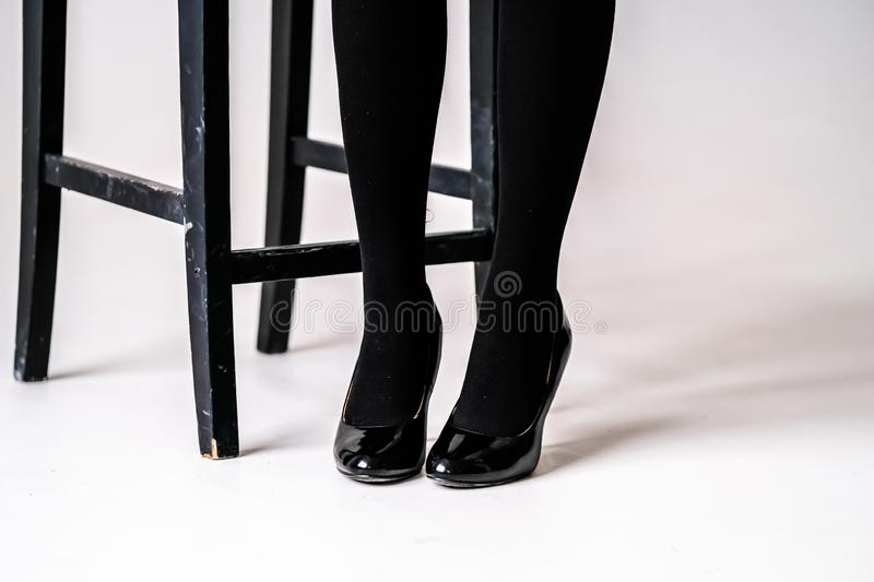 Women`s feet in black stockings or tights. Black high-heeled shoes stock photography