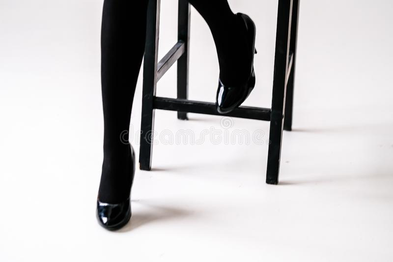 Women`s feet in black stockings or tights. Black high-heeled shoes royalty free stock images