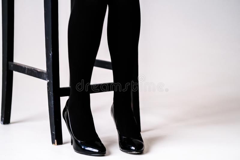 Women`s feet in black stockings or tights. Black high-heeled shoes royalty free stock photos