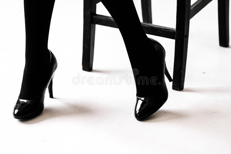 Women`s feet in black stockings or tights. Black high-heeled shoes stock photos