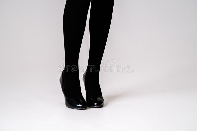 Women`s feet in black stockings or tights. Black high-heeled shoes stock photo