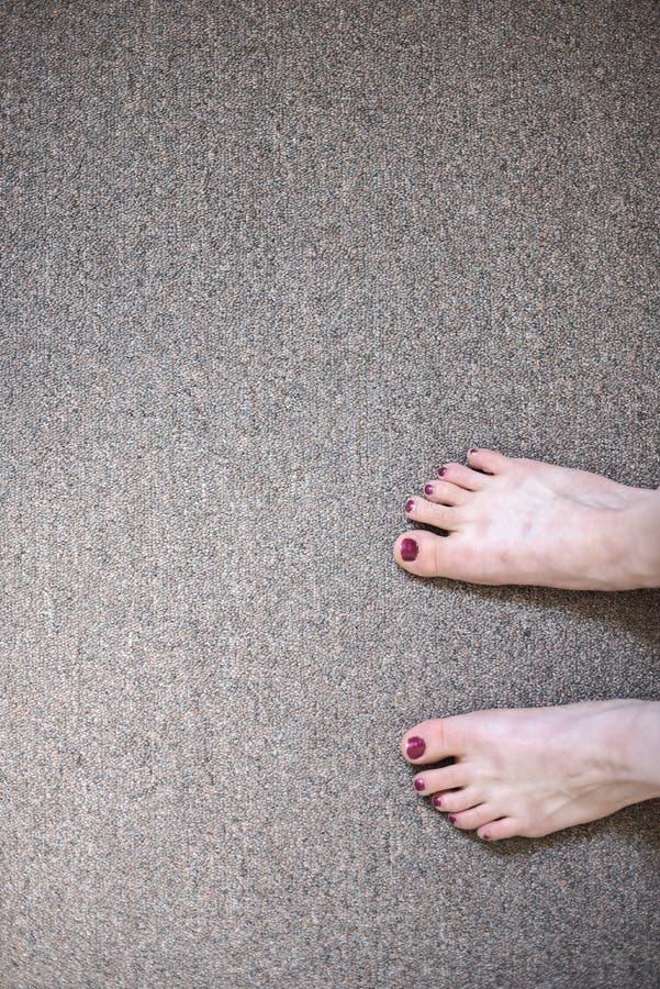 Women`s feet against a grey floor. royalty free stock photos