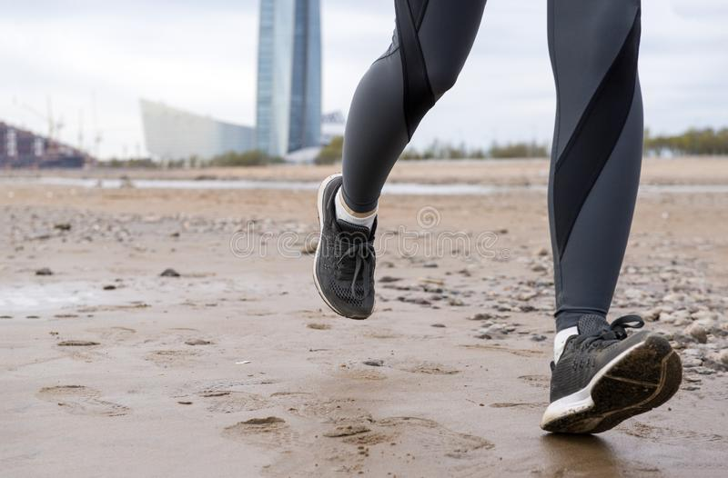 Women`s feet in dark leggings and black sneakers on the sand, running on wet sand, girl running on the beach stock photos