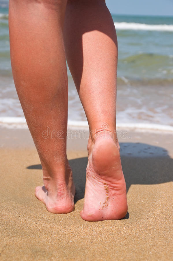 Women's feet going to the sea. Women's legs go to the sea on the yellow sand against the sky stock image
