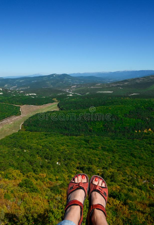 Women& x27;s feet with red pedicure in red sandals over a high cliff against the backdrop of mountains. And blue sky, beauty, toe, woman, female, perfect royalty free stock photo