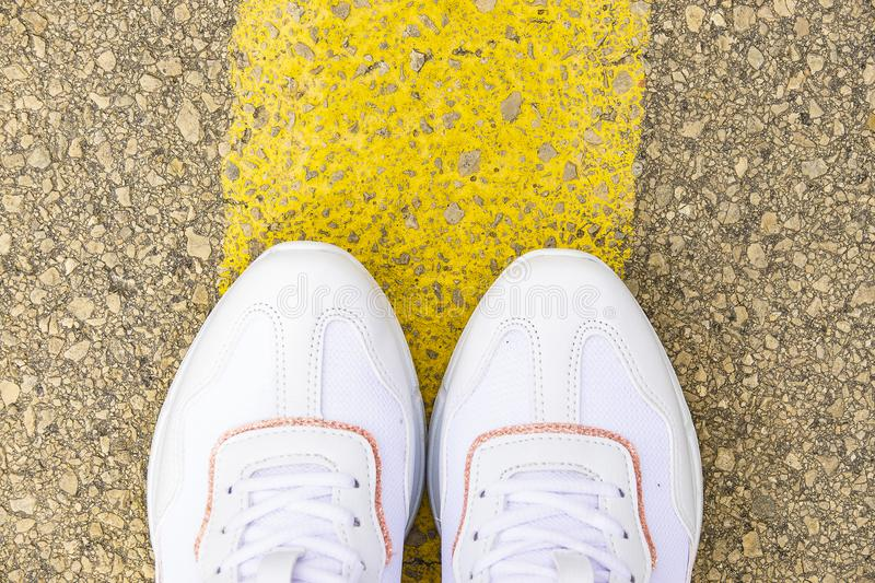 Women`s feet on the road. White sneakers on asphalt top view stock images
