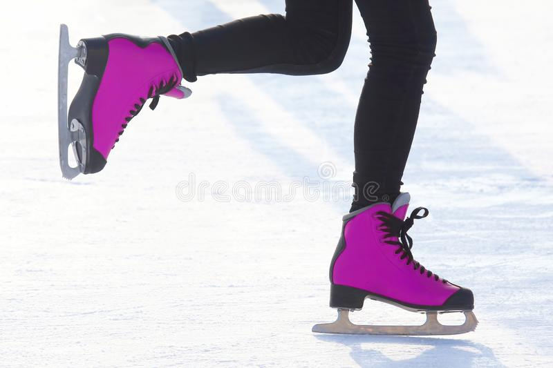 Women`s feet skating on the ice rink. Hobbies and recreation. Sports and holidays. The Women`s feet skating on the ice rink. Hobbies and recreation. Sports and royalty free stock photos