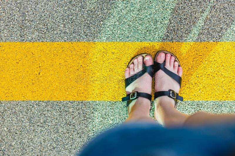 Women`s feet in slippers standing at the yellow line on asphalt. Personal perspective of person looking at his feet royalty free stock image