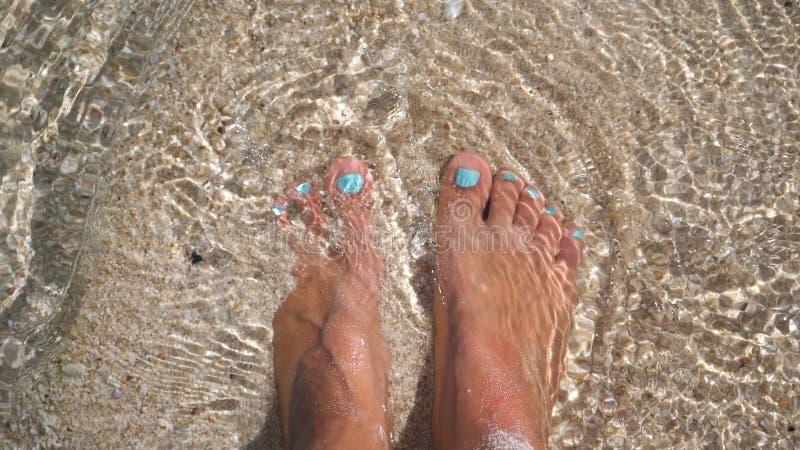 Women`s feet splashing in sea clear water on tropical beach. stock photography