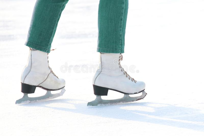 Women`s feet in white ice skating on ice rink. Sports, Hobbies and recreation of active people stock photo