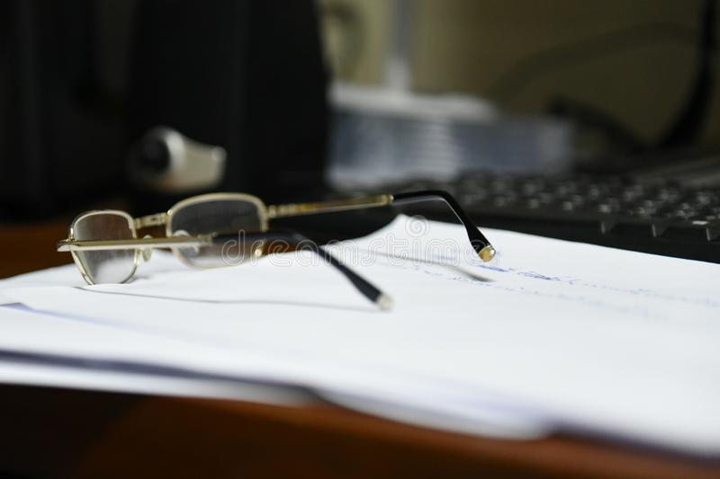 Women glasses placed on white paper on the computer desk with keyboard stock image
