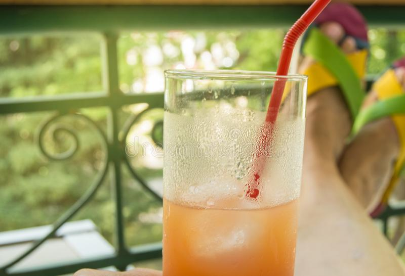 Women`s hand holding a glass with a straw and a cocktail with orange juice of tropical fruits on background of feet, sitting on royalty free stock photography