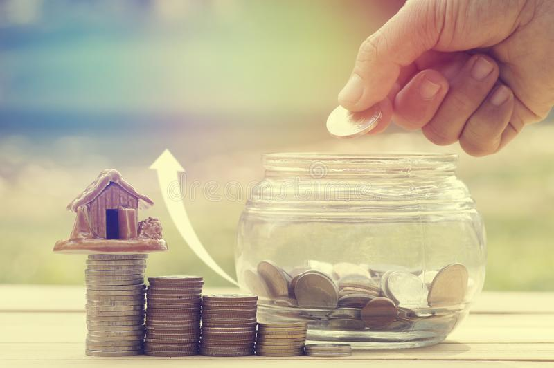 Women & x27;s hand put money coins in glass bottle for save. And donation concept for buying house on wood table, green garden background royalty free stock photography