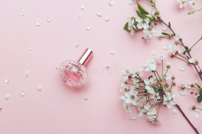 Women`s hand spray perfume. Flower arrangement. Flowers, fragrance, perfume on pink background royalty free stock photography