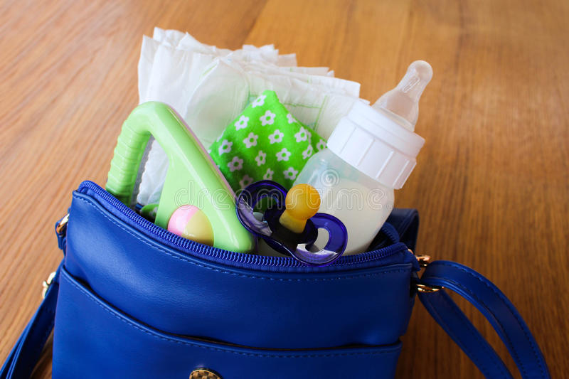Women's handbag with items to care for the child: bottle of milk, disposable diapers, rattle, pacifier and baby clothes. stock photos