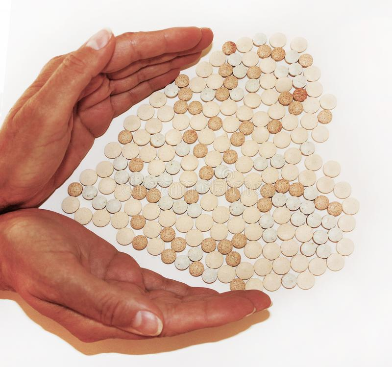Medicines protected by the palms of a doctor, pills lying in the shape of a heart. royalty free stock photography