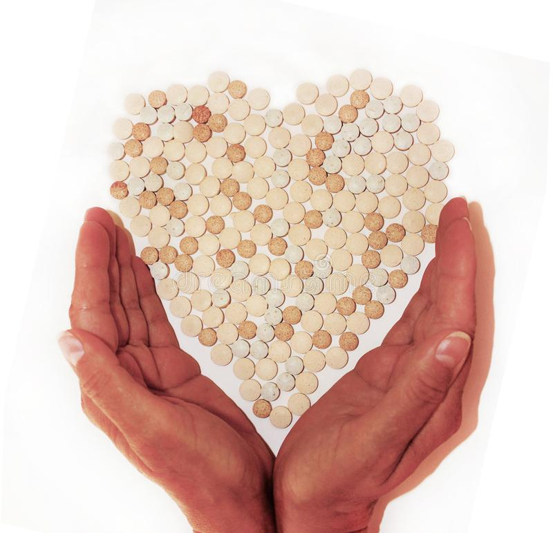 Women`s hands carefully hold pills lying in the shape of a heart. royalty free stock photos