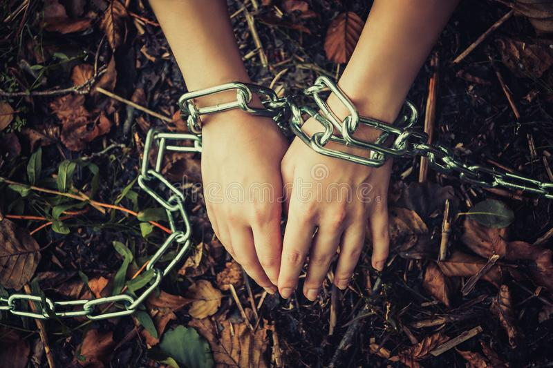 Women`s hands chained in a dark forest - the concept of violence, hostage, slavery stock images