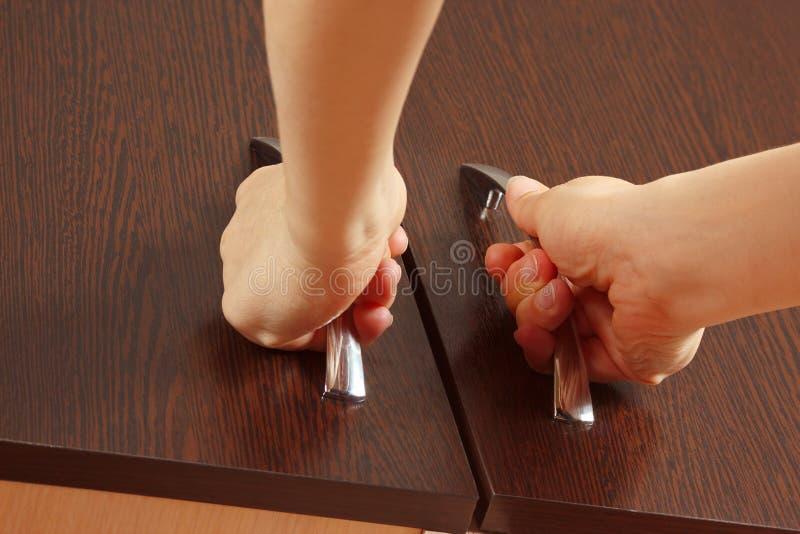 Women's hands closed cabinet doors. Dark wood stock images