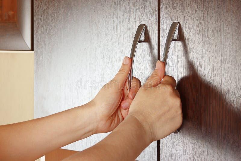 Women's hands closed the cupboard doors. Dark wood stock photography