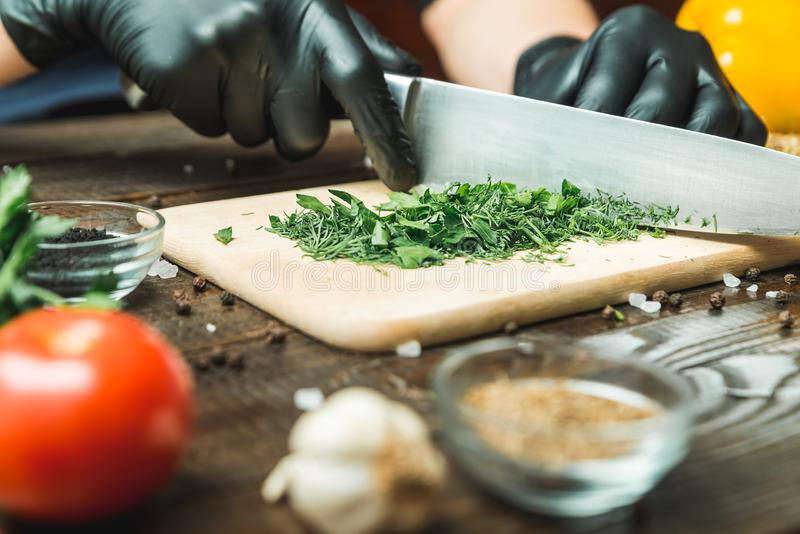Women`s hands cut herbs, next to them are tomatoes, paprika, cucumbers. On whole frame royalty free stock photography
