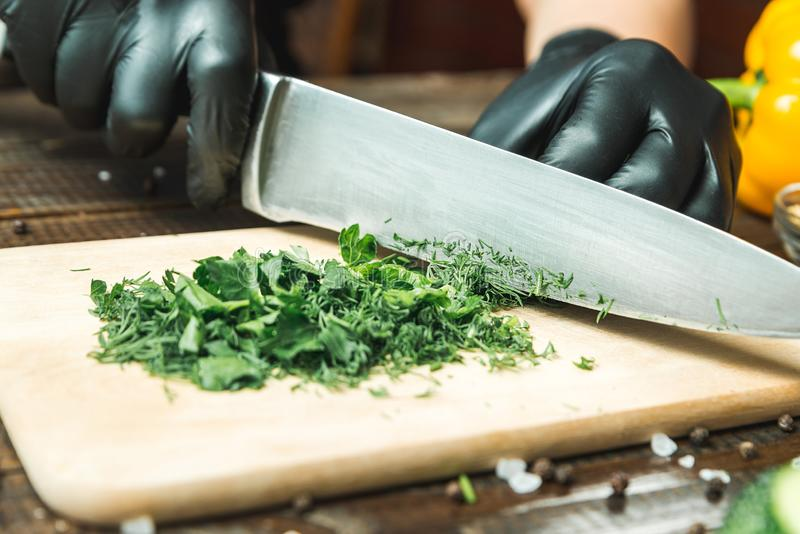 Women`s hands cut herbs, next to them are tomatoes, paprika, cucumbers. Horizontal frame royalty free stock photography
