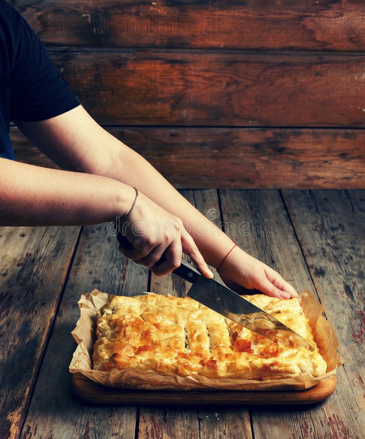 Home cooking. Women`s hands cut homemade pie with stuffing. Celebrating the Day of Independence of the United States. Women`s hands cut homemade pie with stock photo
