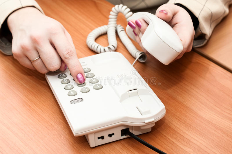 Women's hands dial a telephone number. On the white telephone royalty free stock image