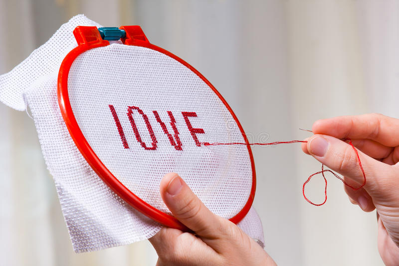 Women's hands embroider cross-stitch a word love. Women's hands embroider a word love on canvas stock photo