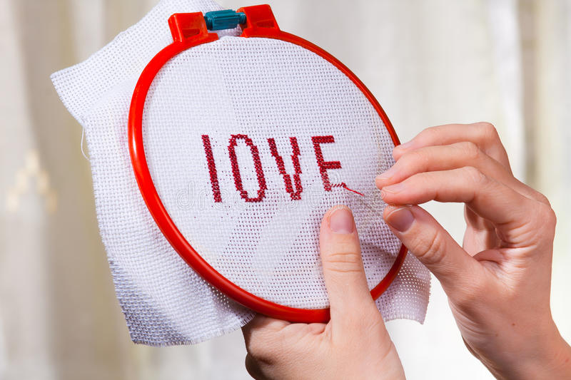 Women's hands embroider a word love. On canvas stock photography