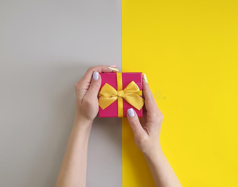 Women`s hands, gift box on a color festive birthday creative decoration celebration royalty free stock photos