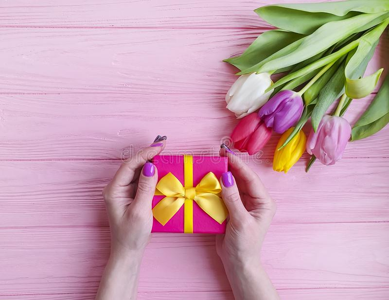 Women`s hands hold anniversary beauty a gift box holiday march birthday, present a bouquet of tulips on a pink wooden background royalty free stock images
