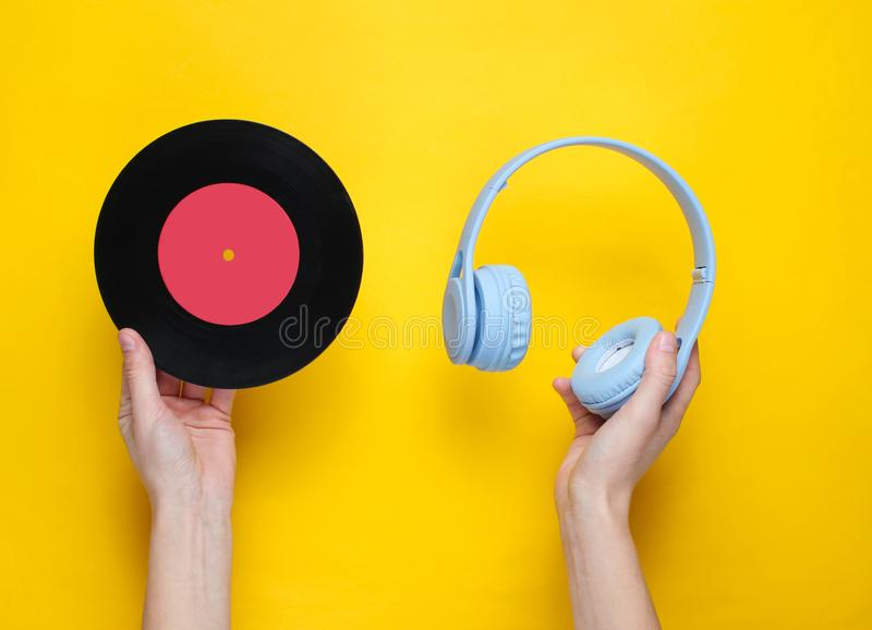 Women's hands hold over-ear headphones and vinyl record royalty free stock photography