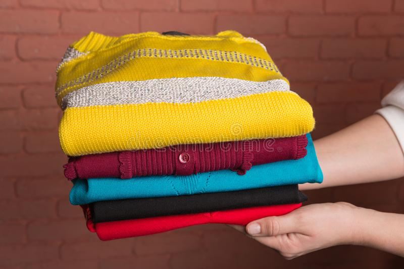 Women`s hands hold a stack of folded colored women`s sweaters, against the backdrop of a terracotta brick wall, the royalty free stock photos