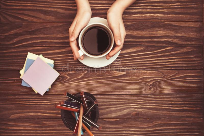Women`s hands holding coffee Cup stickers and pencils on wooden background with copy space on top royalty free stock images