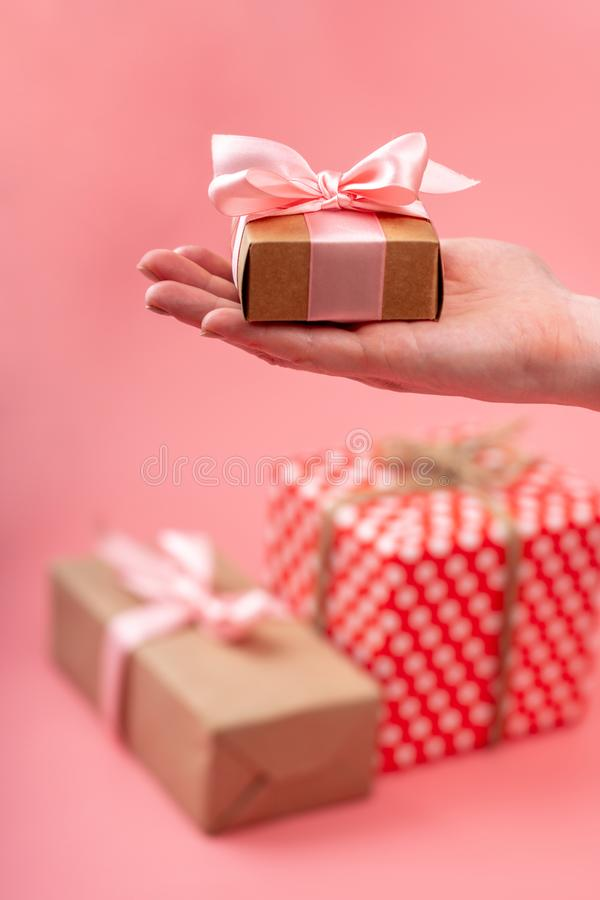 Women`s hands holding gift box Packed in Kraft paper on pink background. Holiday card for Valentine`s and women`s day stock photo