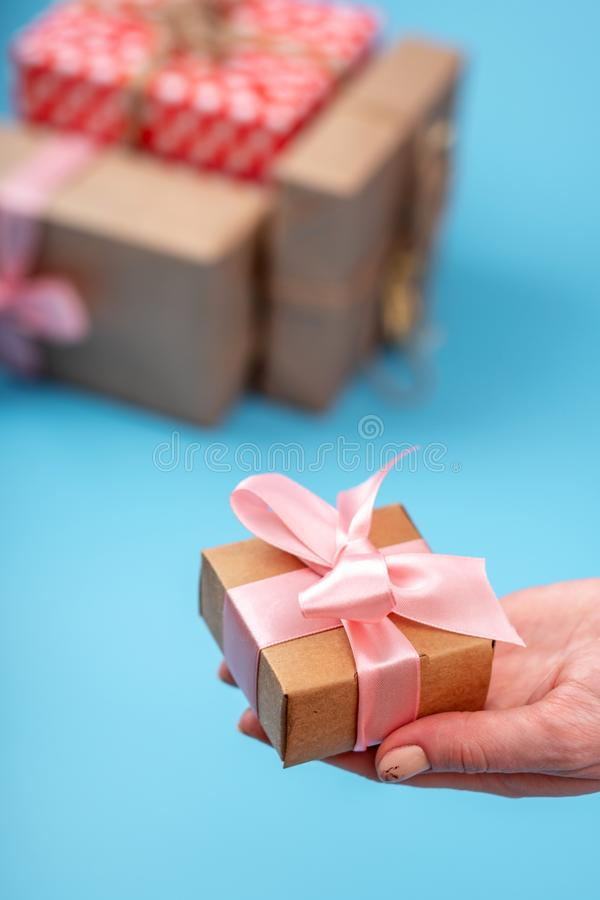 Women`s hands holding gift box Packed in Kraft paper with pink ribbon on blue background. Holiday card for Women`s day stock photography