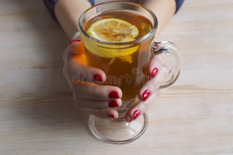 Women`s hands holding glass of tea with lemon stock photography