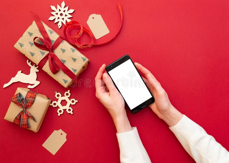 women`s hands holding phone on red background with Christmas decorations and gifts. Xmas and Happy New Year composition. Flat lay royalty free stock photography