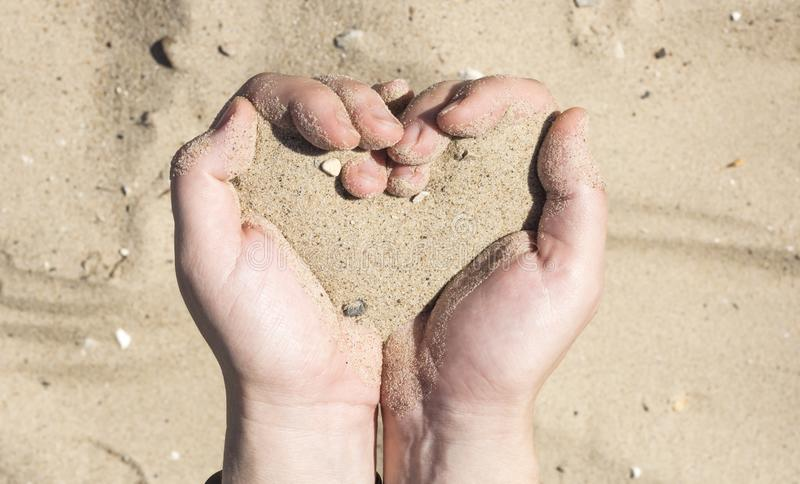Women`s hands holding sand in his hands in the shape of a heart,the concept of life running out like sand through fingers stock photography