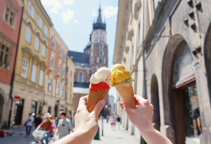 Women`s hands with ice cream on the background of the city sights Mariatsky church in the historical center of Krakow, Poland, royalty free stock photography