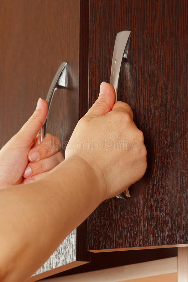 Women's hands are open cabinet doors. Dark wood royalty free stock images