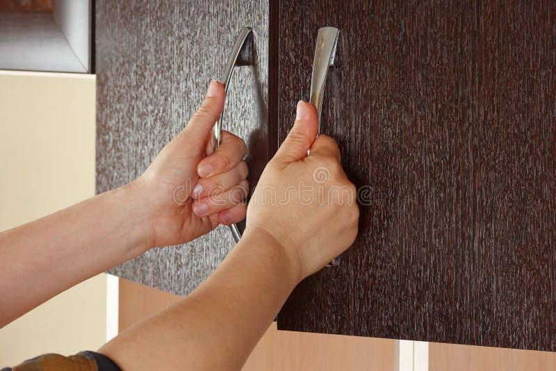Women's hands are open the cupboard doors. Dark wood stock photography