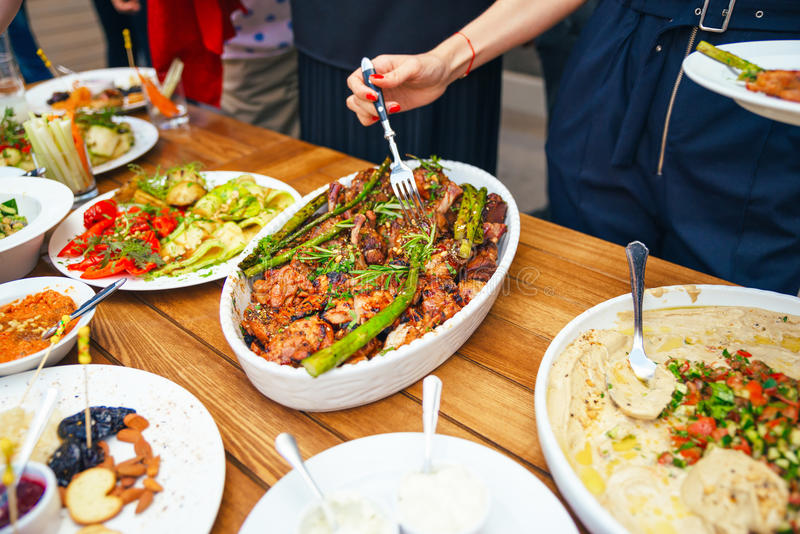 Women's hands pile themselves a meal in a plate of lunch. The concept of nutrition. Buffet. Food. Dinner. The concept of sharing. Close-up stock photo