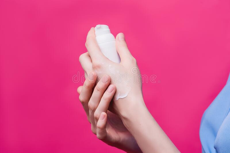 Women`s hands with pink manicure applying cream. The concept of skin care. Women`s hands with pink manicure applying cream. The concept of skin care royalty free stock images