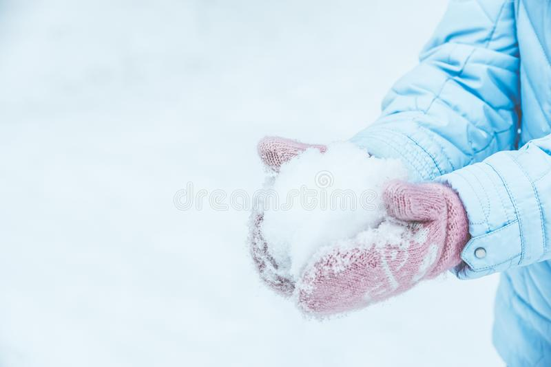 Women`s hands in pink mittens make a snowball for outdoor play in the winter in the forest, Toned and matte.  stock images