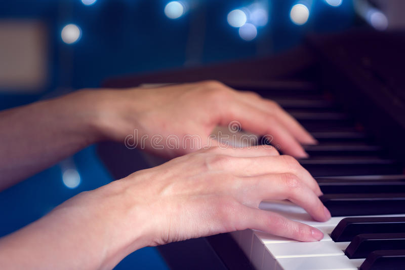 Women`s hands playing the piano stock photos