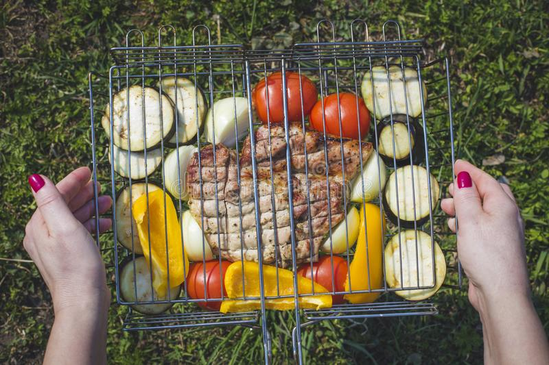 Women`s hands prepare vegetables and meat for grilling. Picnic stock photography